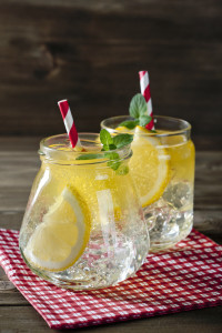 Refreshing cocktails in mason jars over wooden background