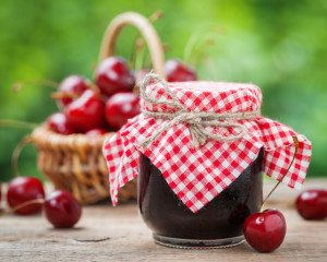 Jars of jam and basket with cherry on background.