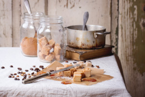 Fudge candy, coffee beans and caramel on baking paper, served over white tablecloth with vintage knife, jar of brown sugar and old pan