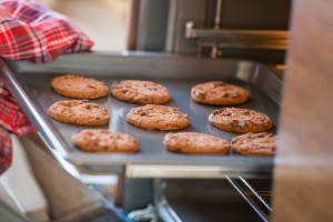 Cropped image of hand removing cookie tray from oven in kitchen