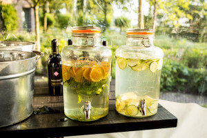 Infused water bottles in party tent orange and lemon water with small taps wine in background