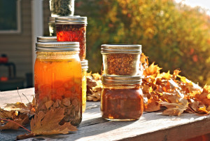 Jars of home canned food on a picnic table in autumn