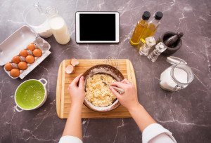 Woman preparing dough from recipe on her tablet