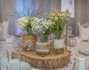 Lovely wedding table centrepiece, showing beautiful flowers in a unique wooden plinth and jars.