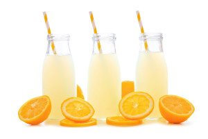Three bottles of cold lemonade with lemon slices and straws isolated on a white background
