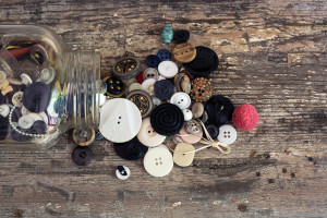 Overhead shot of a clear mason jar full of vintage buttons spilling out onto a rustic wooden table. Natural light.