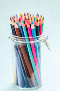 drawing pencils in glass jar on pastel background