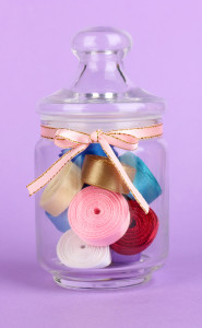 Glass jar containing various colored thread on yellow background