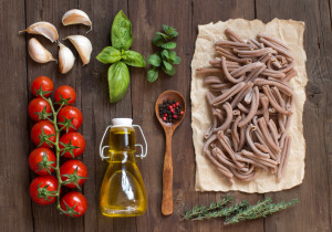 Whole wheat pasta, vegetables, herbs and olive oil on wooden background