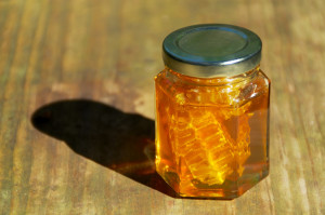 A jar of pure amber colored local honey glistens in the sun, inside the jar is also a piece of the honeycomb it came from.