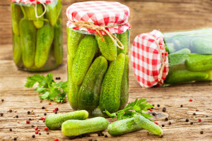 Jars of pickled marinated cucumbers on rustic table