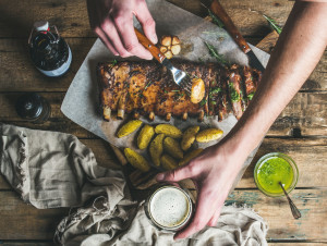 Man eating roasted pork ribs with garlic, rosemary and green herb sauce on rustic wooden table. Man' s hands holding fork with fried potato and glass of dark beer, top view