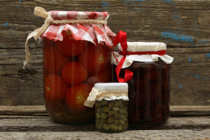 Preserve. Jar with strawberry jam, pickled tomatoes and capers on wooden background