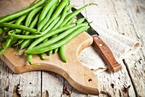 green string beans and knife closeup on wooden board