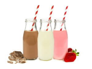 Various flavors of milk in bottles with chocolate and strawberries isolated on white
