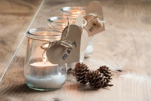 Custom and eco candle holders with jars and paper labels printed for a Christmas dinner