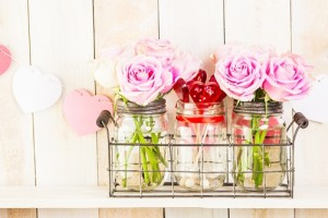 Pink roses in jars on rustic wood shelf for Valentines DAy.